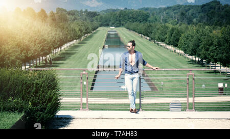 Handsome muscular man posing in European luxury garden - Stock Image