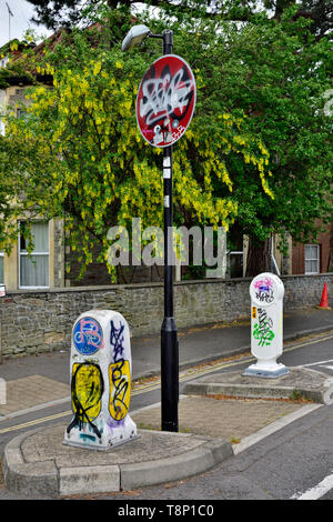 Modern British traffic signs and bollards vandalized with tagging and graffiti - Stock Image