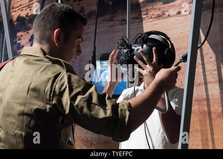 Jerusalem, Israel. 26th June, 2019. Visitors experience parachuting in a virtual reality based simulator. 'Our IDF' exhibition opens at the First Station in Jerusalem featuring armored combat vehicles, an F16 fighter jet, an audio video presentation and combat simulators based on virtual reality. The conscription based IDF, considered in Israel the 'people's army', opens its doors to the public free of charge fulfilling its role in creating a close bond with the public. Credit: Nir Alon/Alamy Live News. - Stock Image