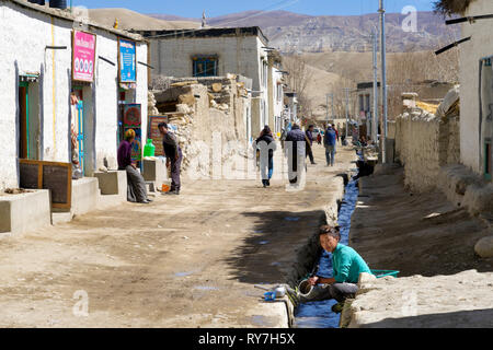 Young Loba woman washing dishes in the communal water supply of the fortified city of Lo Manthang, Upper Mustang region, Nepal. - Stock Image