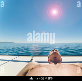 Man on sailboat sunbathing - Stock Image