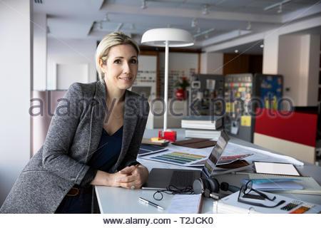 Portrait confident female interior designer in design studio - Stock Image