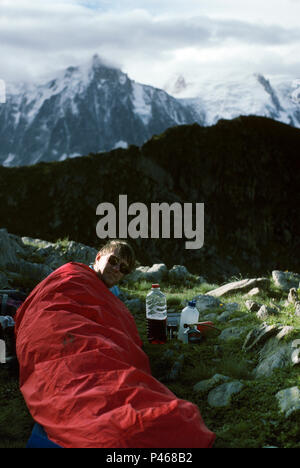 A camper wakes up after spending a night out without a tent in the French Alps - Stock Image