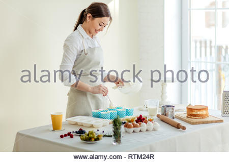 cheerful beautiful female chef using the spoon to scoop cupcake batter, close up side view photo. copy space - Stock Image