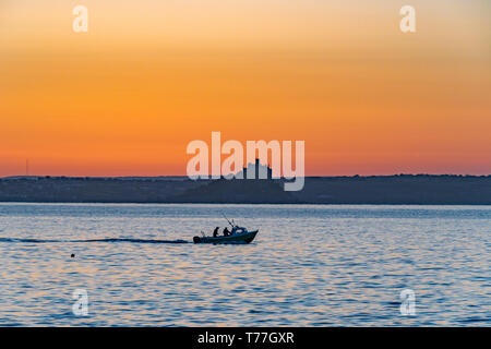 Newlyn, Cornwall, UK. 5th May 2019. UK Weather. With no wind, and calm seas,  this fishing boat headed out to sea from Newlyn harbour just before sunrise this morning.  Credit Simon Maycock / Alamy Live News. - Stock Image