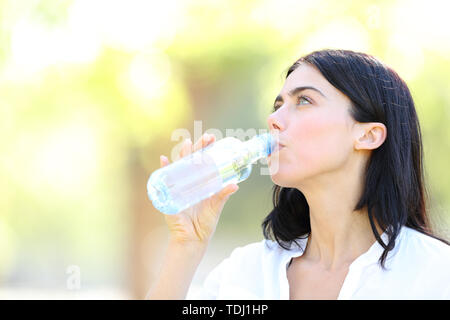 Adult woman drinking water from a plastic bottle standing in a park - Stock Image