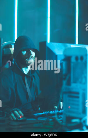 Serious young bearded software engineer in black hoodie sitting in dark room and using modern computer, he working like zombie - Stock Image