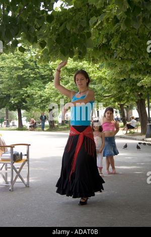 Young Greek woman dances as children look on, Spianada, Kerkyra, Corfu, Greece, Europe, - Stock Image