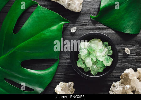 Green Fluorite with Smoky Quartz and Monstera on Black Wood - Stock Image