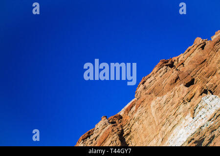 Diagonal rock angle of orange sedimentary cliff face above the mojave Desert in California. - Stock Image