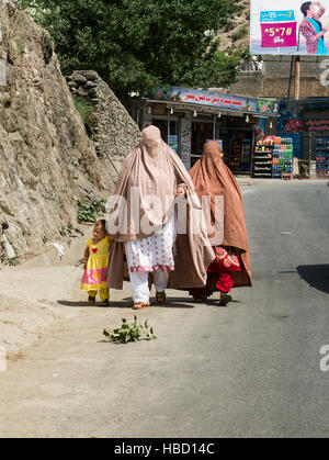 Two women wearing burkhas and a child walking along a road in northern Pakistan - Stock Image