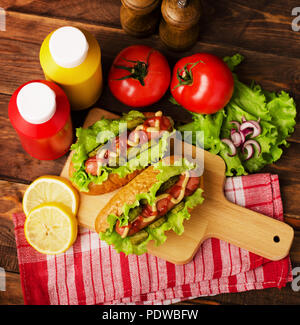 Hot dogs with salad, tomatoes, ketchup and mustard in the kitchen - Stock Image