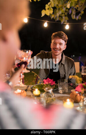 Happy man toasting wine glass at dinner garden party - Stock Image