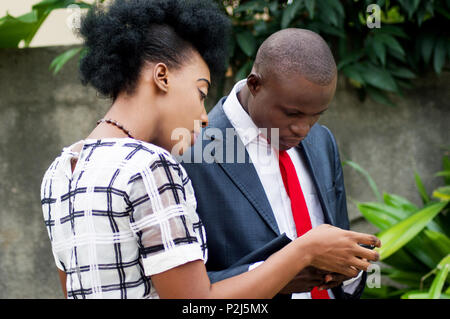 Business people consulting a mobile phone on the street, to see a money transfer. - Stock Image