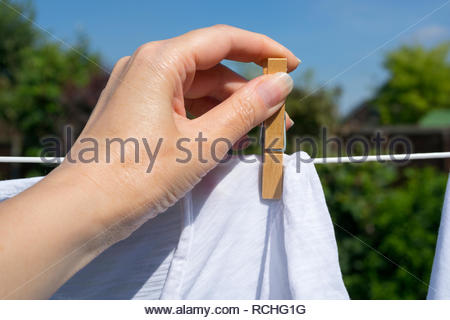 Close up of pegging out washing in the garden - Stock Image