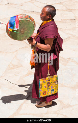 Buddhist monk drumming at a monastery festival at Korzok, a remote hamlet beside (Lake) Tso Moriri in Ladakh, India - Stock Image