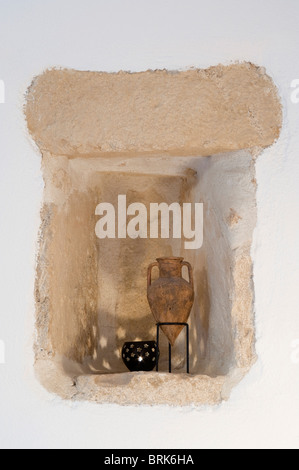 Limestone alcove with Greek urn miniature illuminated by candle in pot with star cutouts - Stock Image