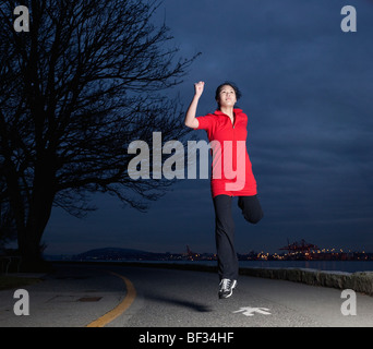 A young Asian woman leaps as she jogs along the Stanley Park seawall at night, Vancouver, British Columbia, Canada - Stock Image