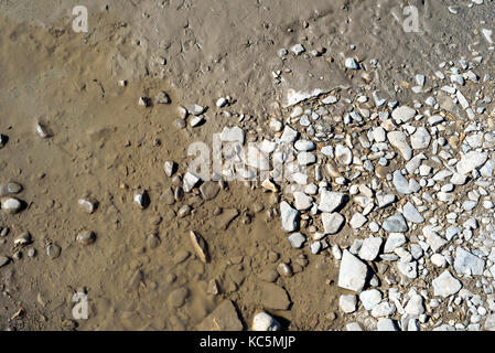 Murky dirty water from a muddy puddle recedes from the edge of stone pebbles as it evaporates due to the heat - Stock Image