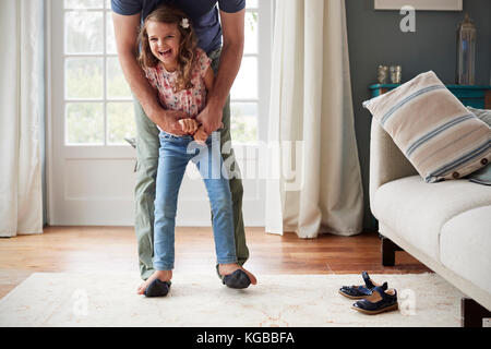 Girl balancing on father's feet at home, looking to camera - Stock Image