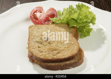 A shot of a slice of bread with a tomatoe and some salad on the side. - Stock Image