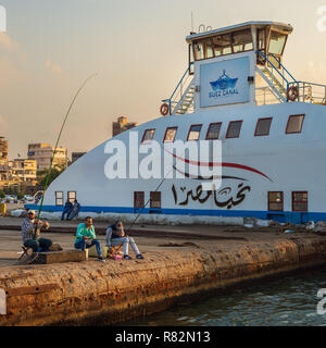 Port Fuad, Egypt - November 10, 2018: Local citizens of Port Fuad district fishing beside Port Said ferry boat at Suez Canal - Stock Image