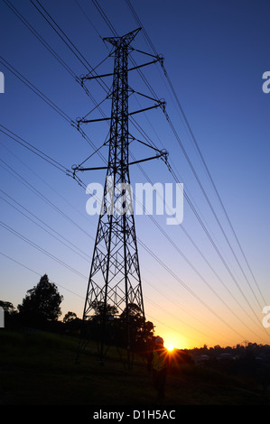 Silhouetted high voltage electricity pylon - Stock Image