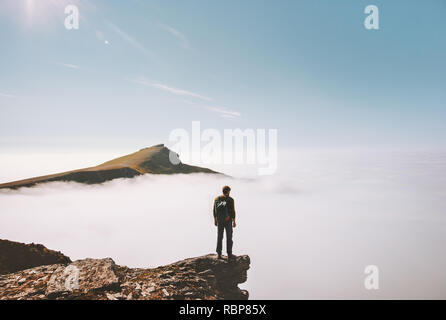 Man explorer standing alone on cliff edge mountain over clouds active travel adventure lifestyle vacations outdoor in Norway - Stock Image