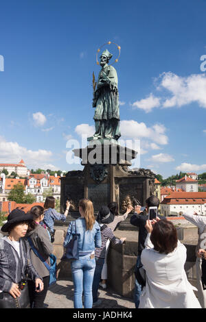 Tourists rubbing the brass reliefs at the base of the statue of St. John of Nepomuk for luck. Charles Bridge, Prague, - Stock Image