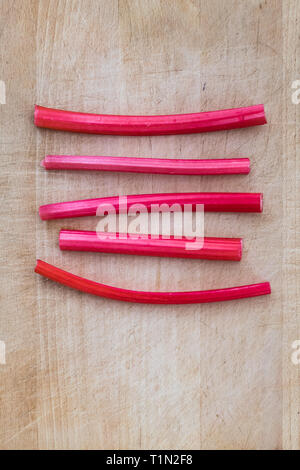 Forced pink rhubarb stalks on wooden chopping board - Stock Image