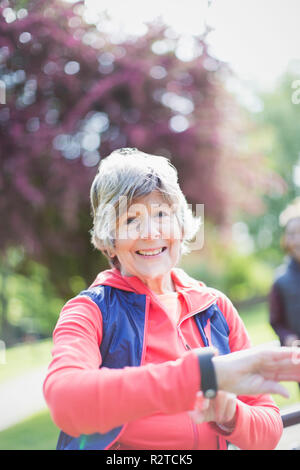 Portrait smiling, confident active senior woman checking smart watch in park - Stock Image