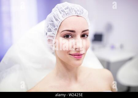 Woman wearing surgical cap in clinic. - Stock Image