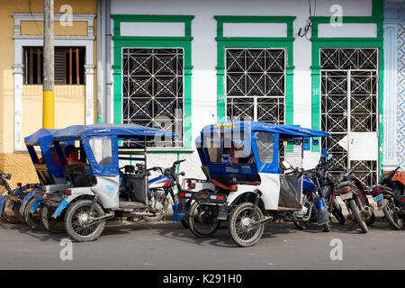 Mototaxi drivers taking a break in the shade in Iquitos, Peru. - Stock Image