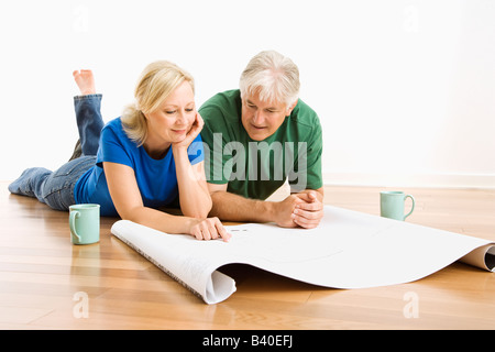 Middle aged couple lying on floor looking at architectural blueprints together - Stock Image
