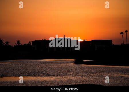 Sunset behind buildings and lake reflection - Stock Image