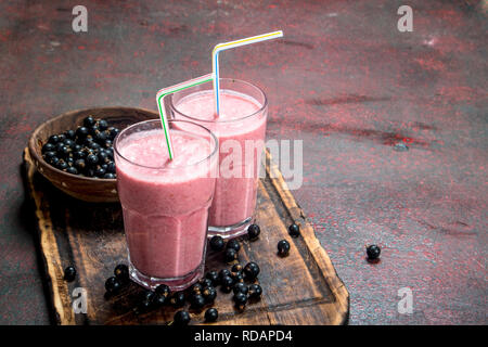 Smoothie with black currant. On rustic background. - Stock Image
