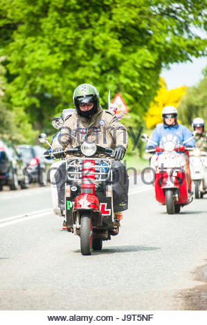 A group or gang of modern vintage aged mods cycling along the Cheshire countryside (Black & White Version)  - Stock Image