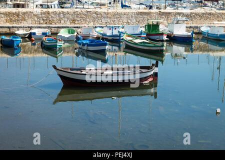 Italy Sicily Syracuse Siracusa Ortygia Porto Piccolo Little Port fishing boats shallow water debris rubbish sea reflection quayside - Stock Image