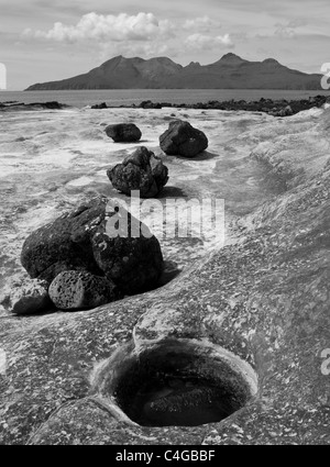 Unusual rock formations at the Bay of Laig on the Isle of Eigg, with the Isle of Rum in the background - Stock Image