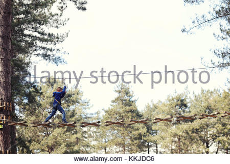 child crossing high rope bridge - Stock Image