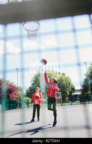 Active senior women playing basketball in sunny park - Stock Image