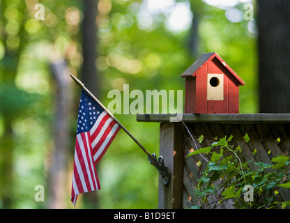 Small red birdhouse on fence near American flag - Stock Image