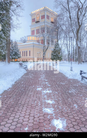 Pedestrian alley in the city park in winter leading to the tower of the Paskevich Rumyantsev Palace - Stock Image