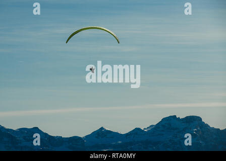 Paraglider in silhouette flies paraglide above beautiful snow capped mountains. Alta Badia, South Tyrol, Dolomites, Italy - Stock Image