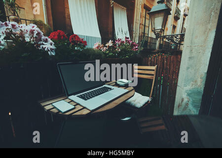 Small cozy beautiful workspace on balcony with laptop, mouse, smartphone, chair, lantern, wooden fence and flowers - Stock Image