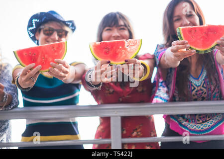 Group of young people caucasian women showing red fresh summer watermelon and smile together in friendship - vacation and holiday leisure activity for - Stock Image