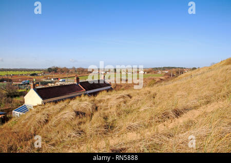 A view of properties on the landward side of sand dunes on the Norfolk coast at Sea Palling, Norfolk, England, United Kingdom, Europe. - Stock Image