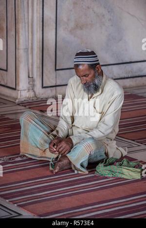 Man sitting cross-legged praying at the Jama Masjid mosque, Old Delhi, India - Stock Image