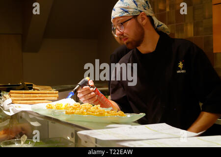 A sushi chef using a blowtorch to sear squid (Ika) in Mikado sushi restaurant in Montreal - a technique known as Aburi - Stock Image