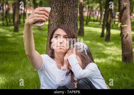 Young mom and little girl takes selfie together.Little girl hides her face.Photo of young mother and her daughter having selfie on green grass - Stock Image